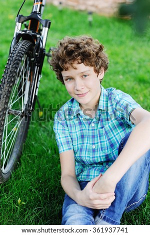 Young teenager bicyclist boy sitting on the grass near his bike in the garden on beauty summer day - stock photo