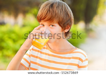 Young teenager boy drinking orange juice outdoors at green background