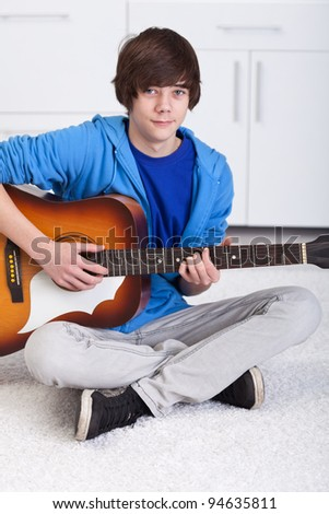Young teenager boy playing the acoustic guitar - stock photo