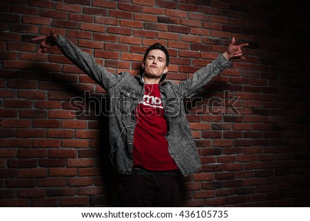 Young teenager dancing with earphones against red brick wall - stock photo