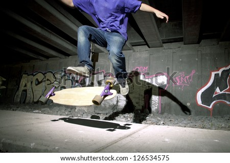 Young teenager flipping his longboard underground - stock photo