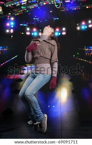 Young teenager girl dancing at night club - stock photo