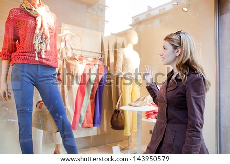 Young teenager girl looking at the clothes in a fashion store shop window in the city, thinking about buying new garments. - stock photo