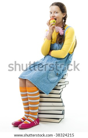 Young teenager girl sit on pile of books and eat apple, isolated on white - stock photo