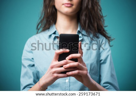 Young teenager girl typing and messaging on her smartphone - stock photo