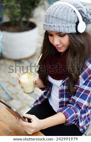 Young teenager girl with headphones using digital tablet computer in coffee shop - stock photo