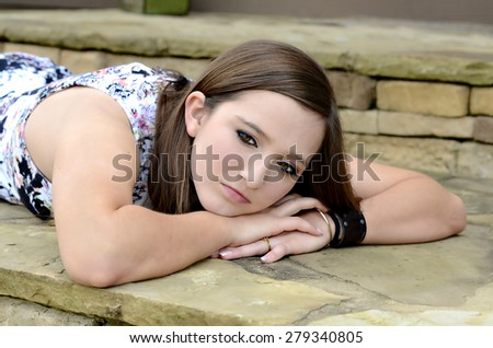 Young teenager lying outdoors with thoughtful expression. - stock photo