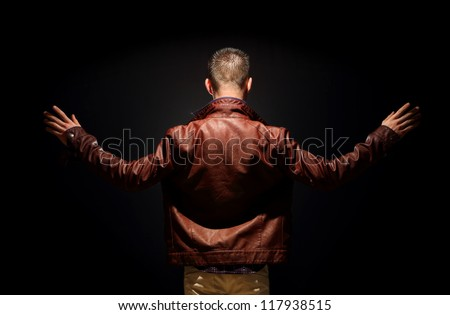 Young teenager on a black background, contrast rear view - stock photo