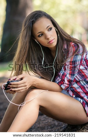 Young teenager portrait listening to music outdoors in a park.  - stock photo