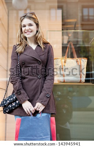 Young teenager tourist visiting the city during the weekend and carrying paper shopping bags while leaning on a fashion store window, smiling and being thoughtful. - stock photo