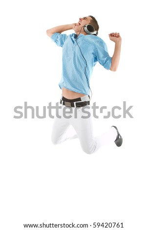 Young teenager with headphones jumping to the music isolated over white background. - stock photo