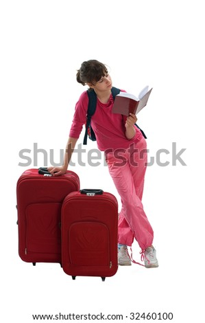 Young teenager with huge luggage while waiting transportation reading book - stock photo