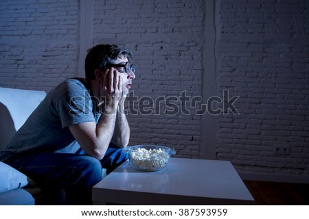 young television addict man sitting on home sofa watching TV and eating popcorn wearing funny nerd and geek glasses looking mesmerized enjoying movie sitcom or live sport at night - stock photo