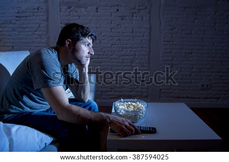 young television addict man sitting on home sofa watching TV eating popcorn using remote control looking bored and tired zapping foe another movie sitcom or live sport at night - stock photo