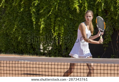 Young tennis athlete ready to return a ball. Elegant girl tennis white dress with skirt swinging racket to hit coming ball green fence background - stock photo