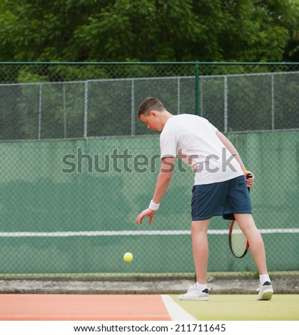 Young tennis player about to serve on a sunny day - stock photo