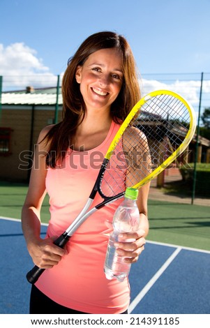 young tennis player holding water bottle. - stock photo