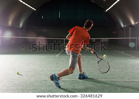 Young tennis player kicking the bal - stock photo