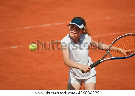 Young tennis talent hitting the ball with backhand slice - stock photo