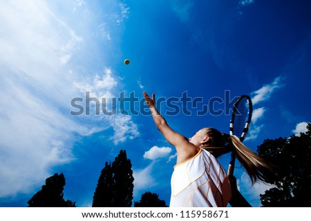 Young tennis woman in a white tennis dress developing ball service - stock photo