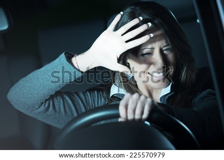 Young terrified woman driving and having a car accident at night. - stock photo