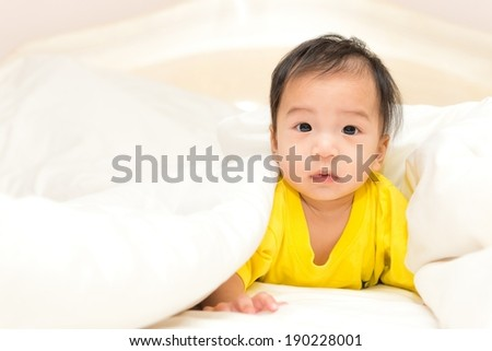Young Thai baby boy in yellow shirt posing various actions, taken indoor - stock photo