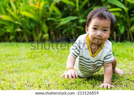 Young Thai baby crawling on green grass, taken outdoor in the afternoon - stock photo