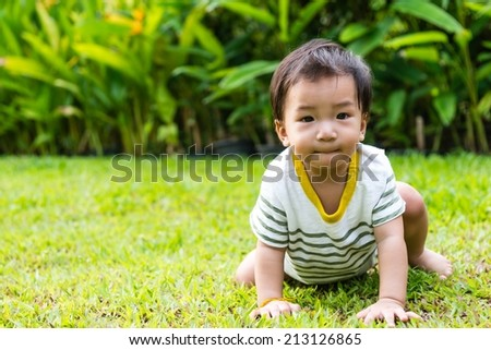 Young Thai baby crawling on green grass, taken outdoor in the afternoon