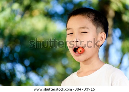 Young Thai boy eat strawberry with happy face.