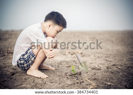 Young Thai boy planting little seedling on dry and crack empty land. Earth day concept. - stock photo