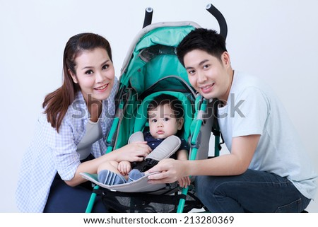 Young Thai dad mom and son in the pram smile happily isolated - stock photo