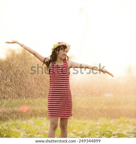 Young Thai lady funny with under rainning - stock photo