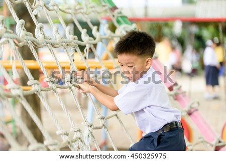 Young Thai student boy in school uniform play alone at the rope net in the play ground.