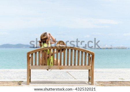 Young Thai woman sit on the wood chair near the blue ocean under the blue sky in the summer.