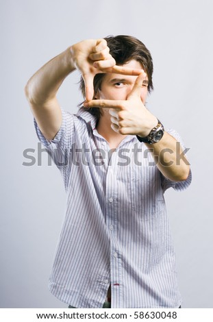 Young the man looks through a frame combined of fingers. - stock photo