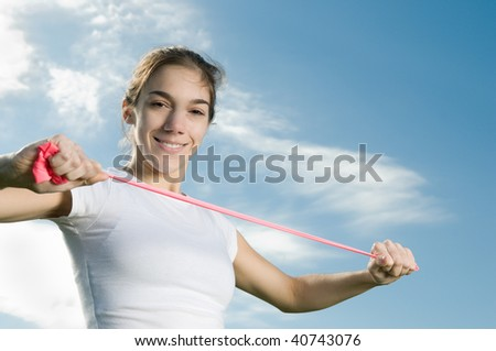 Young thin woman exercising outdoors, doing arm physical therapy with pink elastic band