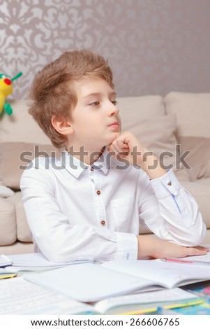 Young thinker. Small schoolboy thoughtfully holds his chin with a hand sitting by the table and doing tasks  - stock photo