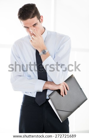 Young thinking businessman standing in office and holding folder.
