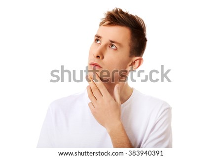 Young thinking man looks up with hand near face