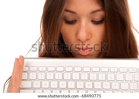 Young thinking woman looking on a laptop computer keyboard isolated on a white background - stock photo