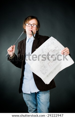 Young thoughtful architect with sketch, studio shot - stock photo