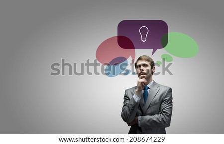 Young thoughtful businessman and colorful speech bubbles above - stock photo