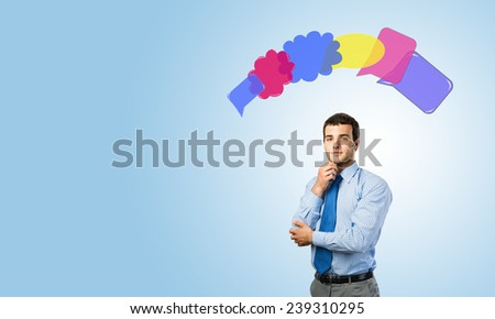 Young thoughtful businessman and colorful speech bubbles above head - stock photo