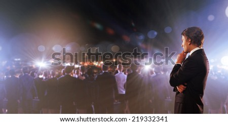 Young thoughtful businessman and crowd of business people - stock photo
