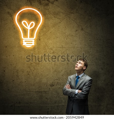 Young thoughtful businessman looking above at light bulb