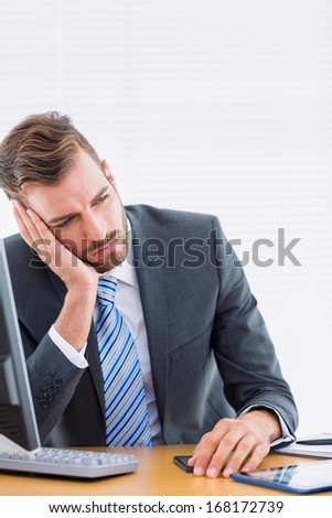 Young thoughtful businessman sitting by computer at office desk