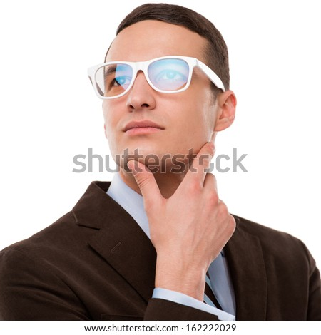 Young thoughtful businessman wearing glasses and holding chin on hand on white background - stock photo