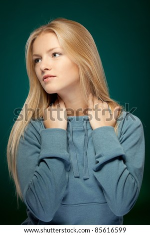 Young thoughtful female looking sideways over dark background - stock photo