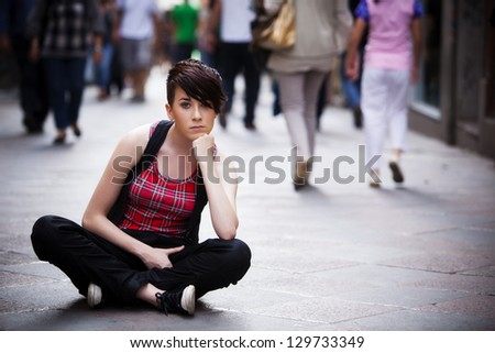 Young thoughtful girl sitting on sidewalk - stock photo