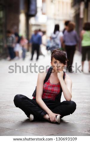 Young thoughtful girl sitting on sidewalk - stock photo